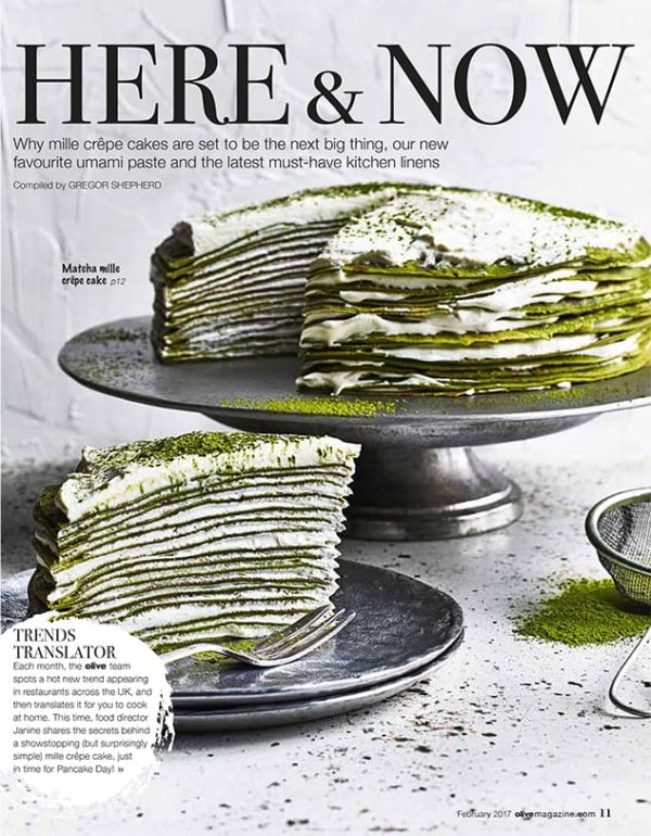 A layered matcha mille crepe cake, with layers of pastry packed with cream filling creating a large tall cake