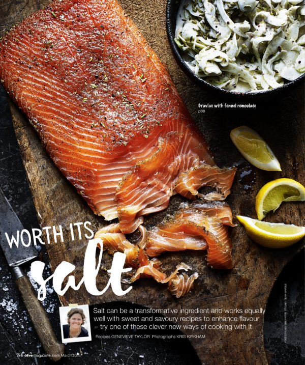 A smoked salmon fillet laid on a wooden chopping board sprinkled with salt and pepper
