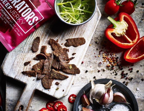 A shot of the sweet Sriracha jerky on a wooden board with the ingredients its made from: Thai-bbq sauce and fresh chillies spread around