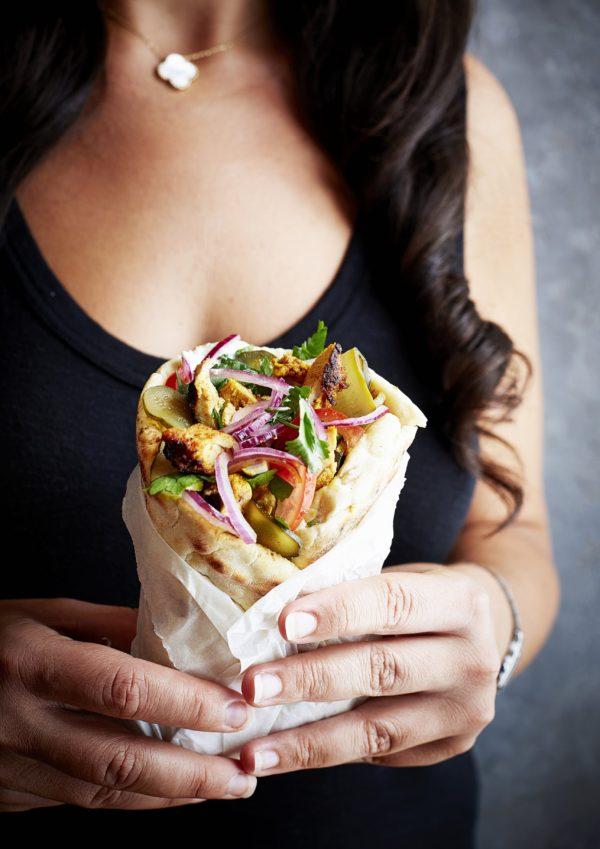 A well-stuffed Chicken Shawarma held by model, ready to be eaten