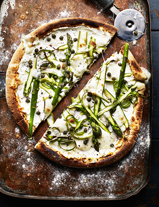 A pizza base on a floured board decorated with cheese and courgette strips