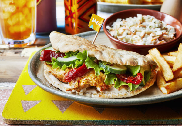 Nando's chicken pitta on a plate, served with coleslaw and chips
