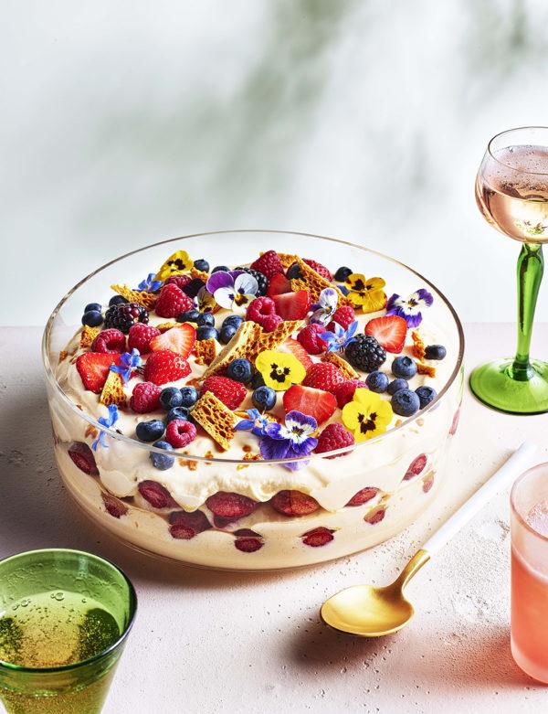 A large layered tiramisu style dessert topped with edible flowers