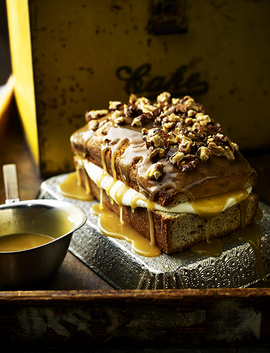 A loaf of walnut cake sat on a baking tin, with the filling spilling out the sides